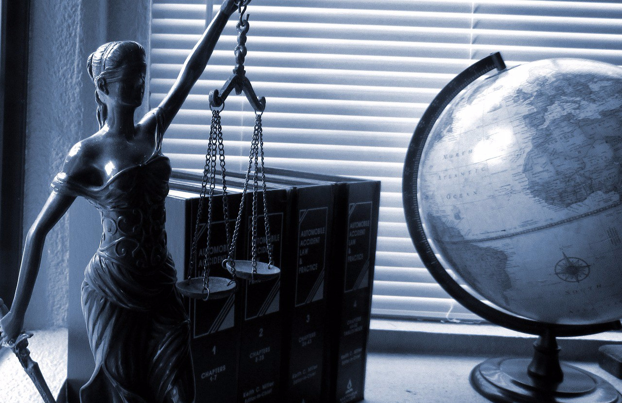 A lady holding scales on the left and a globe on the right