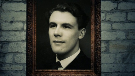 A painted portrait of Leonard Ravenhill in a frame with stone wall behind the picture