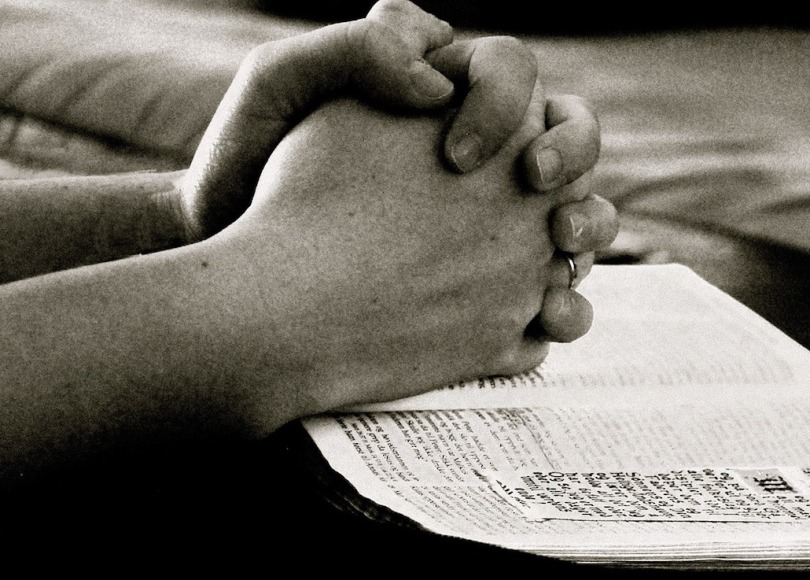 A black and white image of a person's hands locked together praying over a Bible