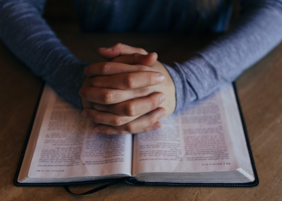 Hands locked together in a praying position resting on an open Bible