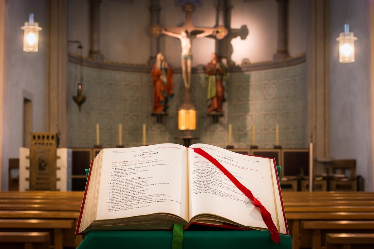 A Bible on a lectern in a church with a statue of Jesus in the background