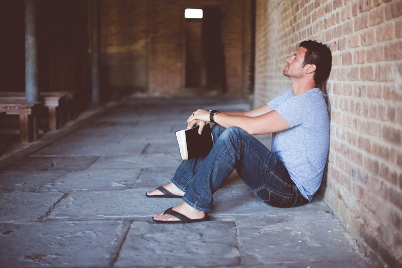 A man sat down with his eyes closed leaning against a brick wall with a Bible in his hand