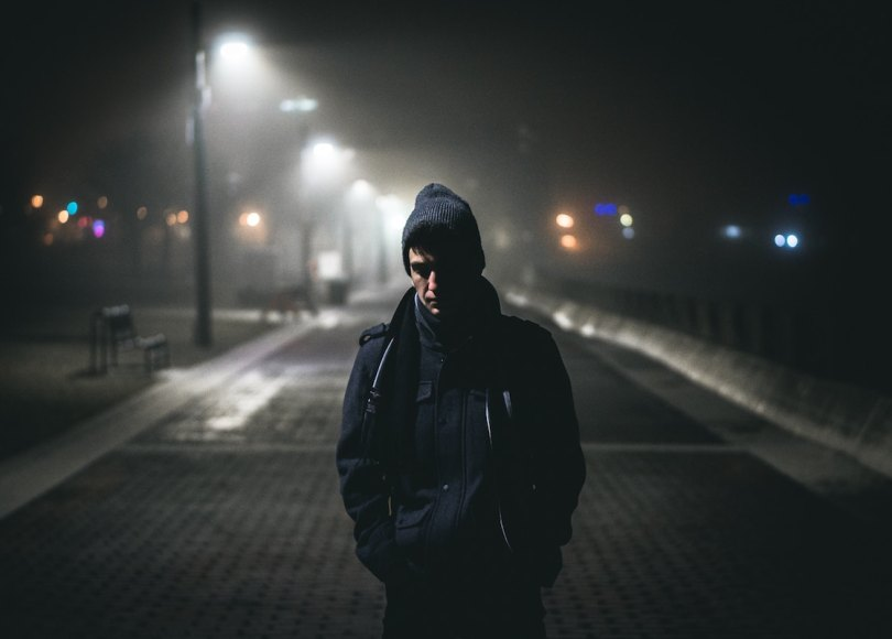 A man on a cold night with street lamps behind him