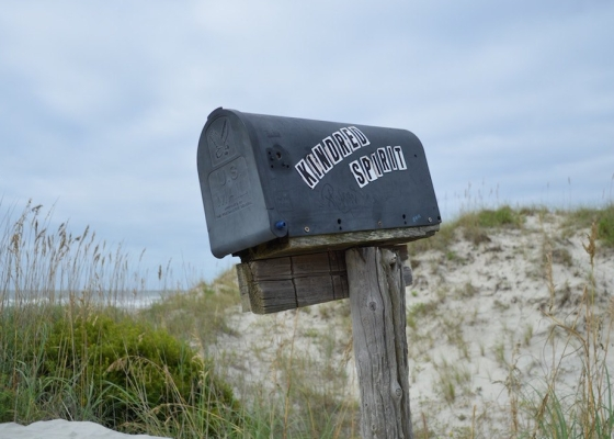 An old-fashioned letter box with a beach in the background
