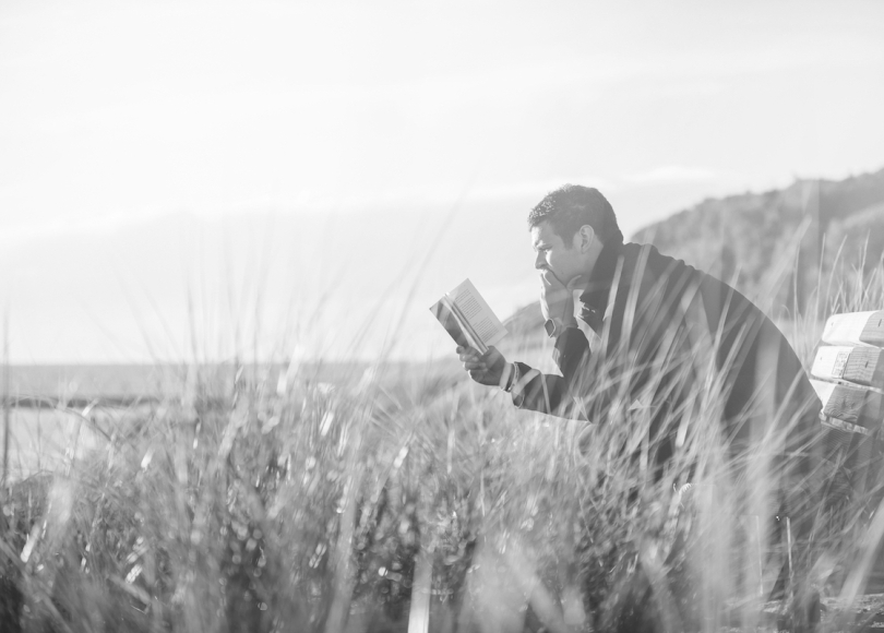 Man reading book black and white