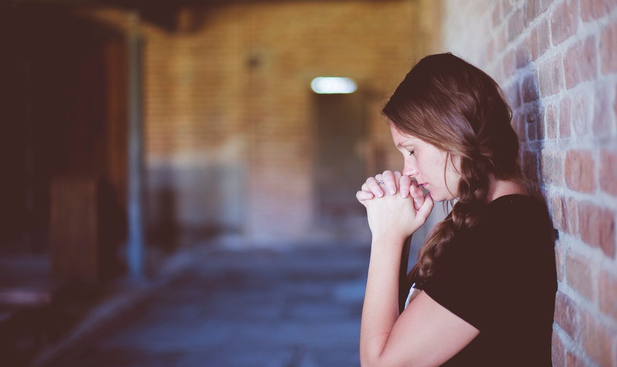 A woman praying with her back against a brick wall