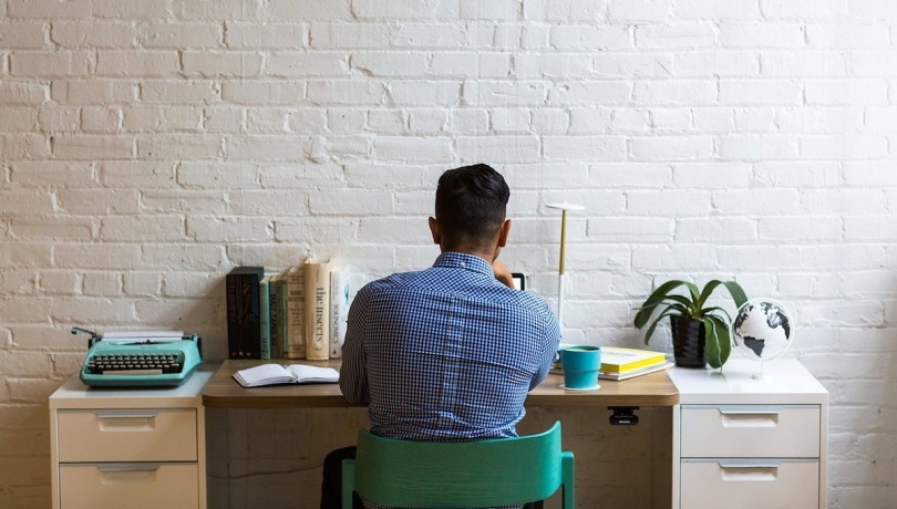 A man working at his desk pictured from behind