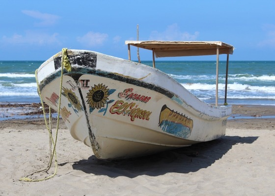 A fishing boat on a beach with the sea in the background