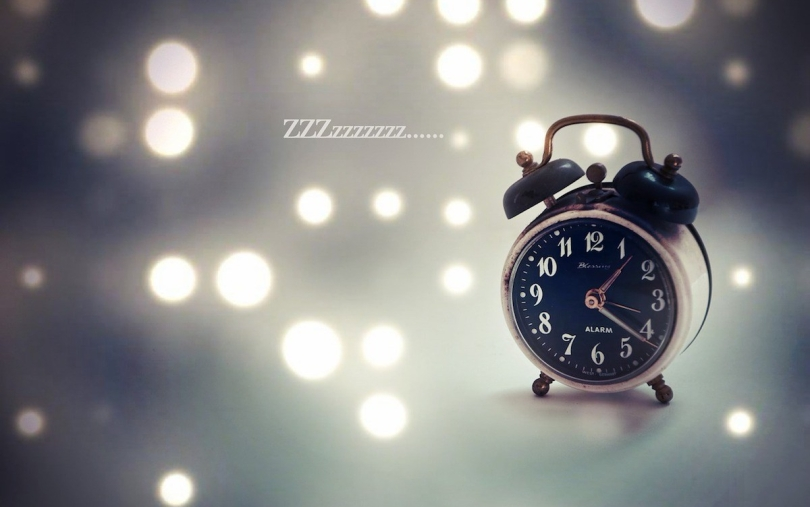 An old-fashioned alarm clock with abstract lights in the background