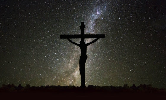 Jesus on the cross in darkness with the universe in the background