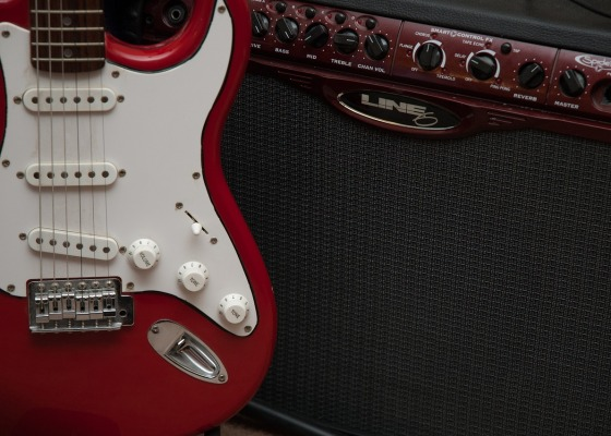 A red stratocaster guitar and a Line 6 amplifier