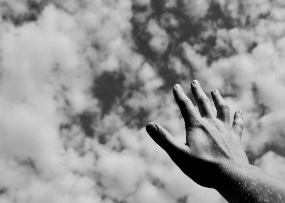 Hand raised to sky black and white