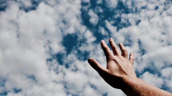 A hand reaching out towards a cloudy sky