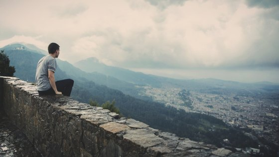 A man sat on a wall looking down on a city on a cloudy day