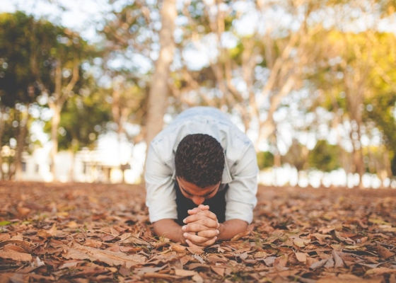 A man on the ground praying