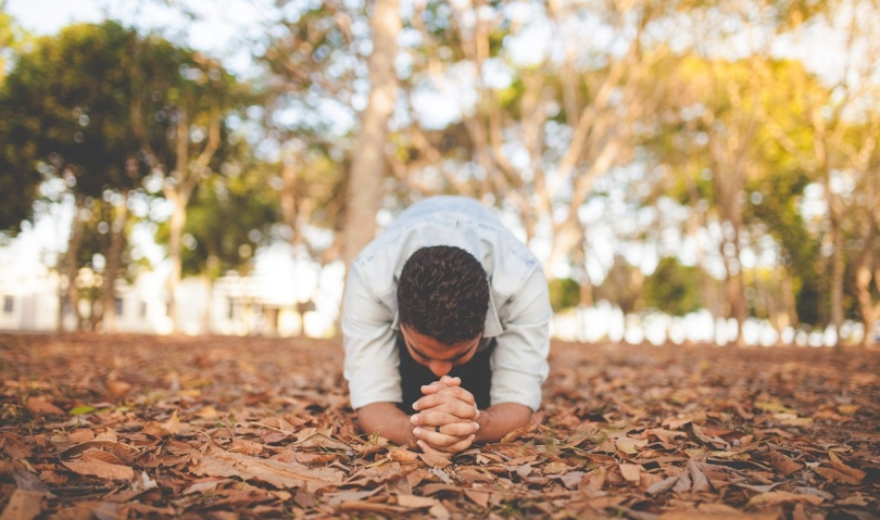 A man on the ground praying
