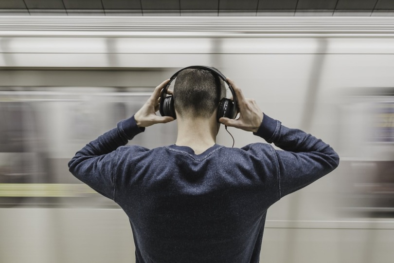 A photo from behind of a man holding headphones to his ears