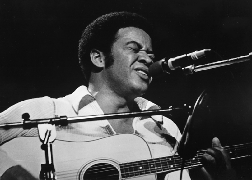 A black and white picture of Bill Withers with an acoustic guitar