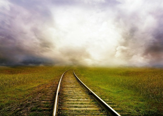 A railway line surrounded by grass leading to clouds