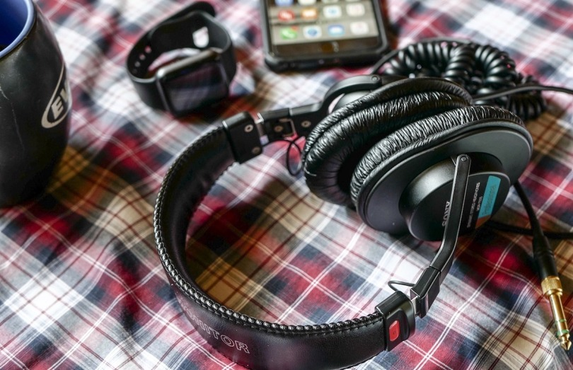 Headphones and tech accessories on a checked tablecloth