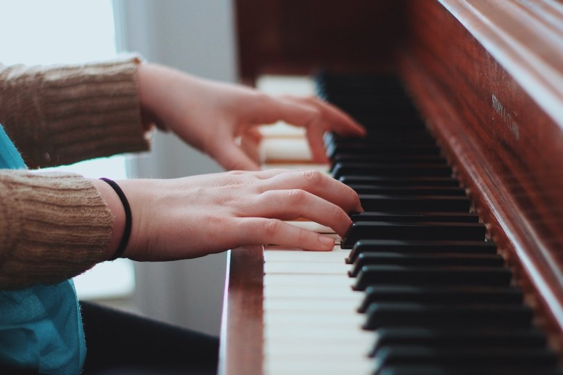 A lady's hands playing a wooden piano