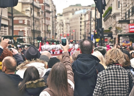 A crowd taking pictures with their mobile phones on the streets of London