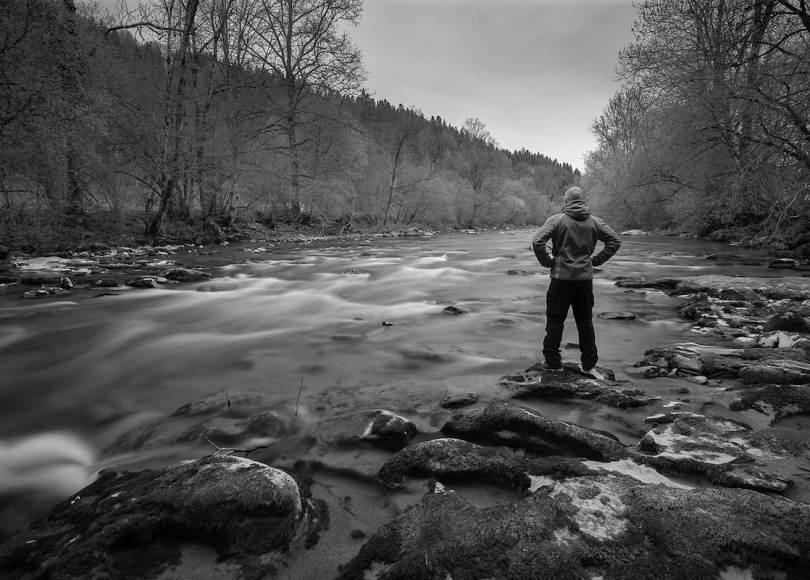 Man by river black and white