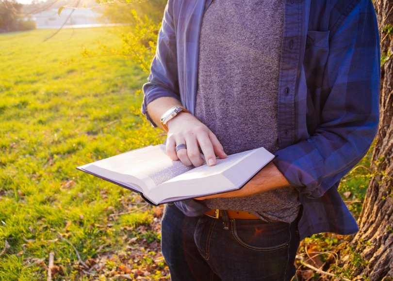 A man pointing to a page in an open Bible