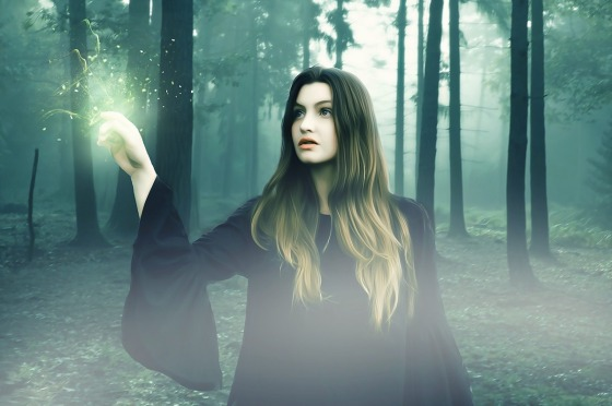 A woman in a forest with light emanating from here finger