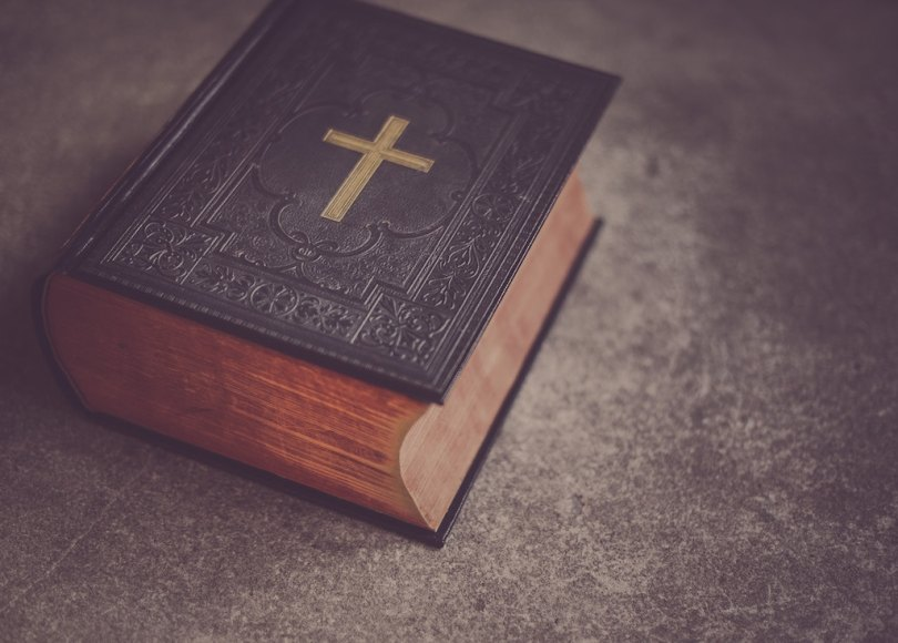 An old Bible with a gold cross on the cover