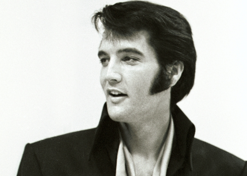 A black and white portrait photo of Elvis Presley