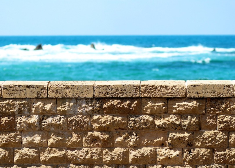 A wall in the foreground and blue sea and sky in the background