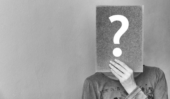 Black and white picture of a person holding up a question mark