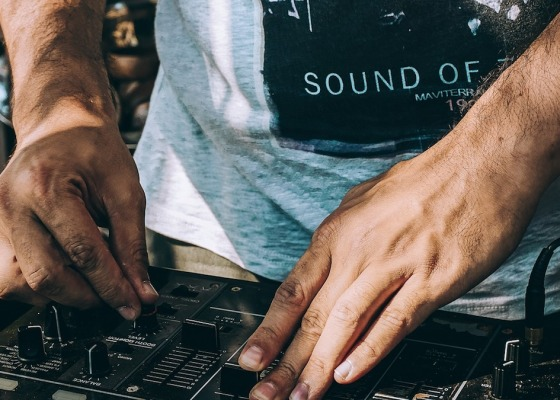 A close-up of a man's hands as he adjusts levels on a mixing desk