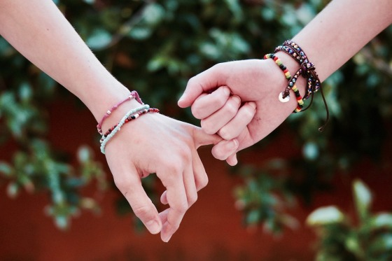Two hands linking fingers with friendship bracelets around their wrists
