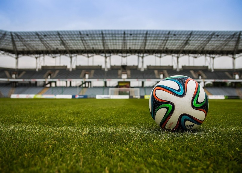 A closeup of a colourful football with a stadium in the background