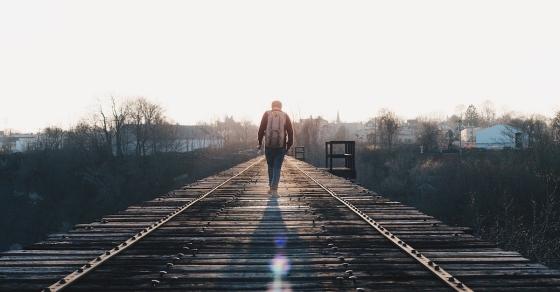 A man walking along a railway track