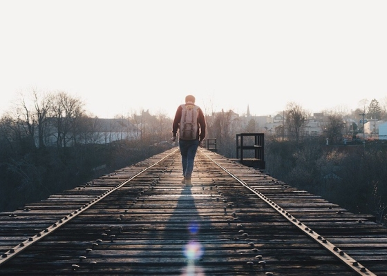 A man walking along a railway track