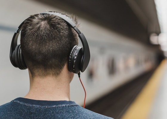 A closeup of a man wearing headphones from behind, next to a blurred-out train