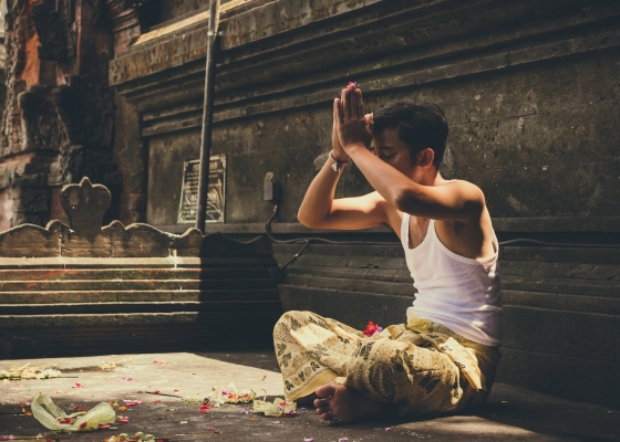 A young man sat cross-legged praying