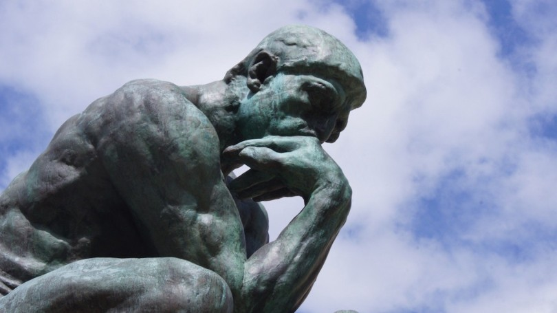 A statue of a thinking man in front of a cloudy sky