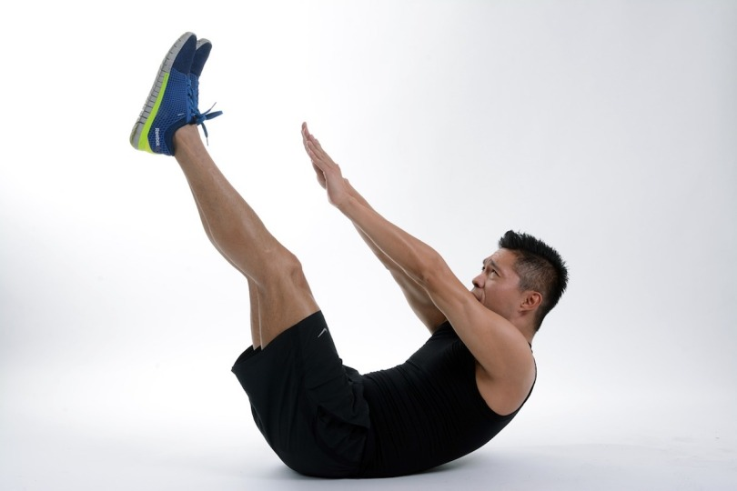A man wearing sports clothes doing a stretch
