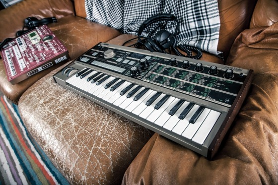 A keyboard and other musical equipment on a brown leather sofa