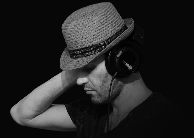 Black and white photo of a man wearing a hat and listening to music