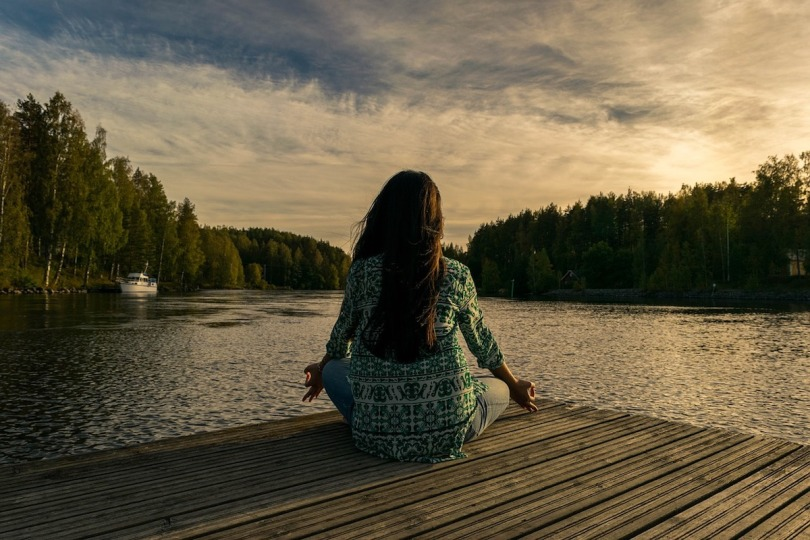A woman sat by a lake in a meditative position