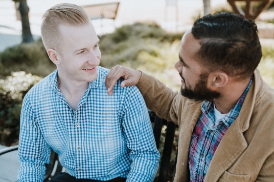 A man with his hand on another man's shoulder. They are in conversation and smiling.
