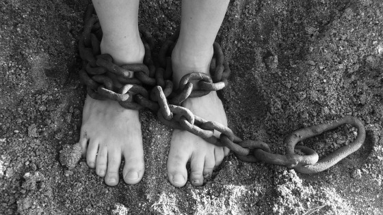 Black and white photo of feet in chains