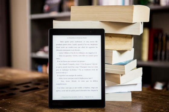 A pile of paperback books with an eReader leaning against them