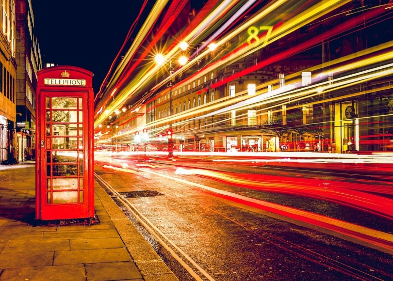 A traditional British phone box on the roadside with lights streaking past