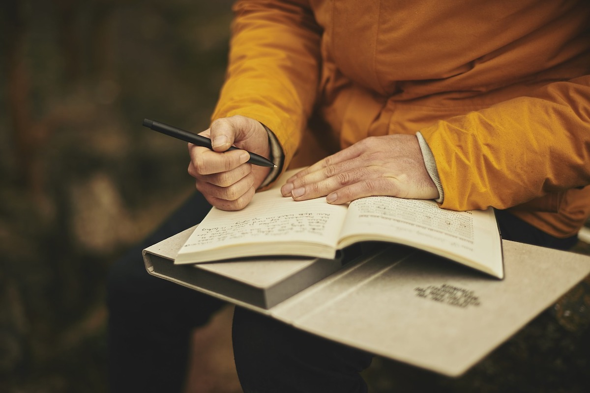 A man wearing orange writing in a notebook